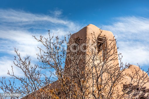 Tower of an old historic adobe church in New Mexico with a painterly sky