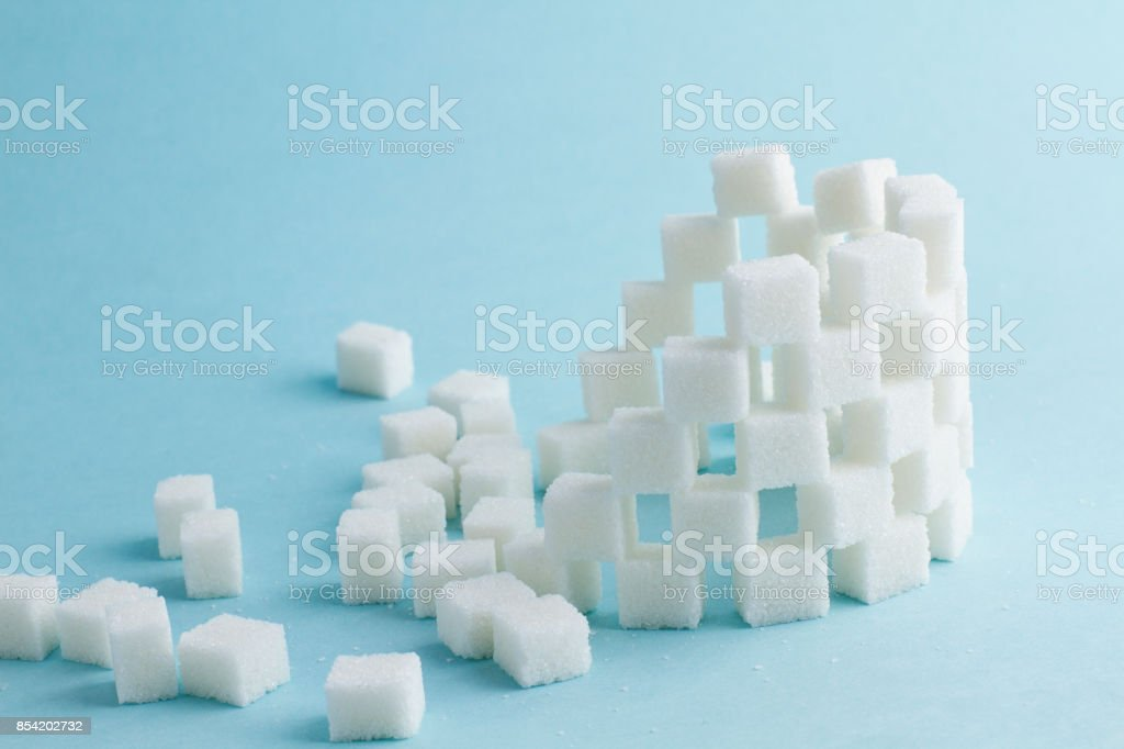 Tower of cubes of sugar on blue stock photo