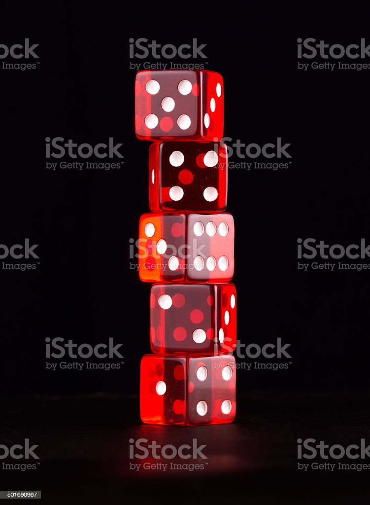 Tower of five red transparent dices on black, isolated royalty-free stock photo