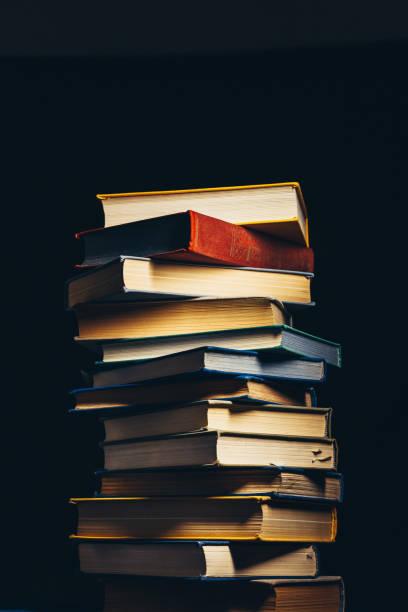 Torre do antigo multi-coloridas livros sobre um fundo preto. Conceito de educação e conhecimento - foto de acervo
