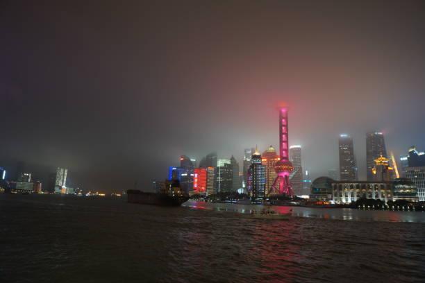 Tower of Shanghai illuminated in fog at night stock photo