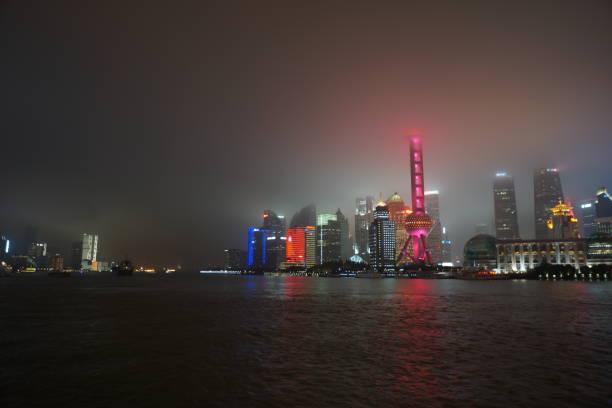 Tower of Shanghai illuminated in fog at night. stock photo