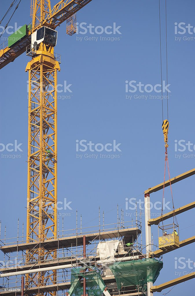 Tower-crane hoisting a basket with workers royalty-free stock photo