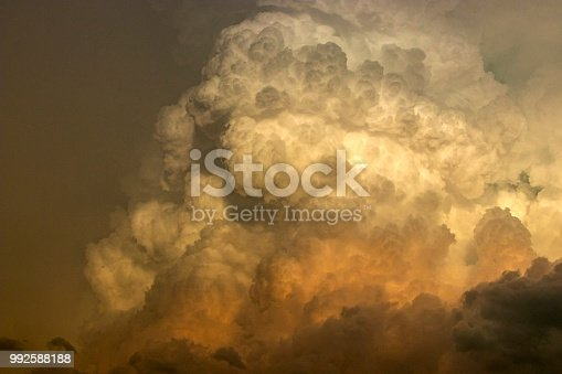 Towering cumulonimbus clouds in billowing updraft at sunset in Kansas