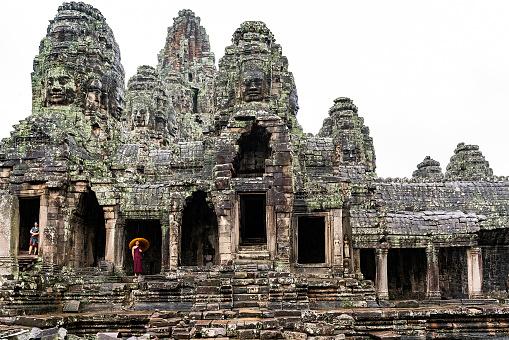 Angkor Vat, Cambodia - September 04, 2019: Towers and Faces at Bayon temple in Angkor Wat. Monk who has umbrella at Bayon Temple with Tourist woman.