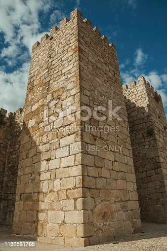 Towers and stone walls facade with merlons on a cloudy day at the Castle, also called Alcazaba, of Trujillo. A small medieval town, birthplace of the Conquistador Francisco Pizarro in western Spain.