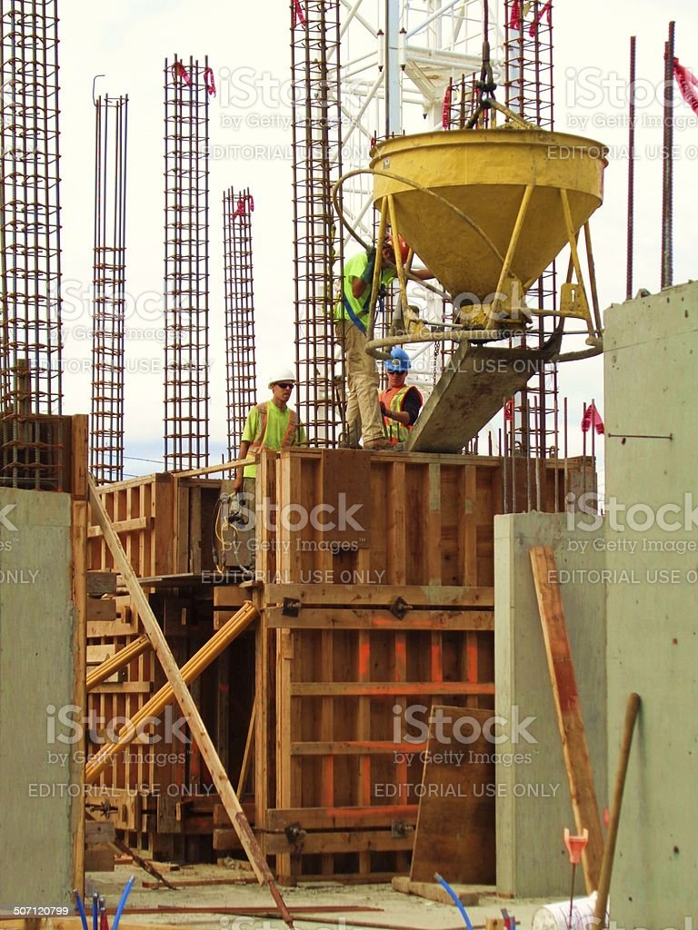 Towers of rebar and cement workers stock photo