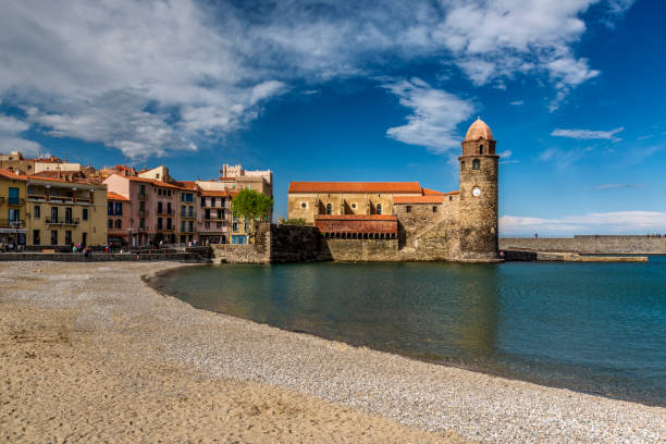 Town beach with Notre Dame des Anges church in the background, Collioure, Pyrenees-Orientales, France stock photo