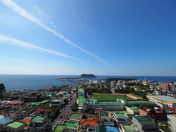 Town by coast line top view of small town besides coast line with blue sky and ocean seogwipo stock pictures, royalty-free photos & images