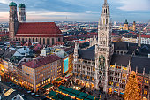 Town hall and frauenkirche Munich, Germany, panoramic view of two famous landmarks with Christmas decoration during sunset.