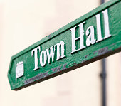 Close-up of a traditional, worn sign showing the direction to the town hall.