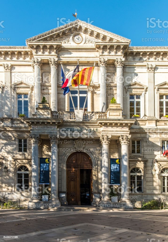 Town Hall in  Avignon with flags and clock stock photo