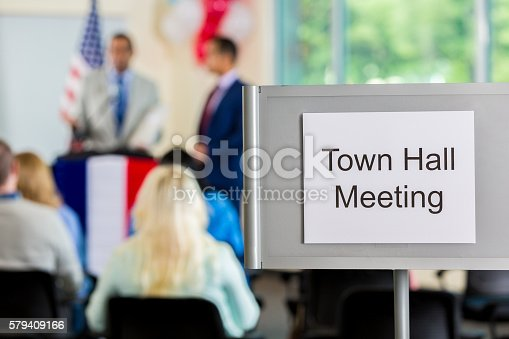 Town hall meeting sign with the town hall meeting proceeding in the background. There is an american flag that can be identified.