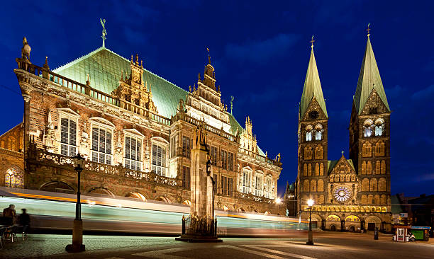 """Town hall of the Hanseatic city Bremen Germany by night """"Bremen, Germany - may 6, 2013: Town hall with the statue of Roland and the Dom in the Hanseatic city of Bremen Germany by night while the tram is passing by. Bremen was in the Hanseatic league and is on the UNESCO world heritage list."""" duitsland stock pictures, royalty-free photos & images"""