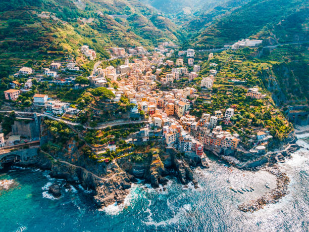 Town in mountains towering over tranquil sea, CinqueTerre, Italy stock photo