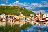 Scenic view of the historic town of Husavik in beautiful golden evening light at sunset with blue sky and clouds, north coast of Iceland