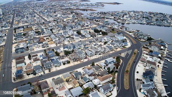 Aerial view of New Jersey shore town, looking south toward Barnegat Bay right and Atlantic Ocean on left with West Point Island far right. Shot from a DJI Phantom4 Pro drone.