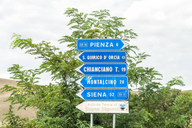 town village in tuscany during sunny summer day and highway road street with blue exit direction sign for pienza and siena - cartello stradale italia km foto e immagini stock