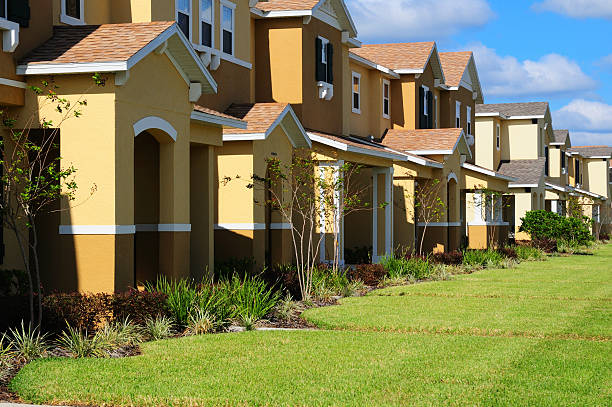 Townhouses Row of identical looking generic townhouses with blue sky and green lawns gated community stock pictures, royalty-free photos & images