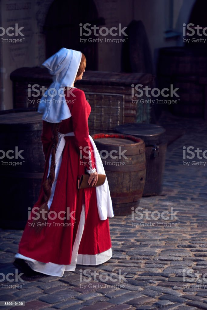 Townswoman in red dress with an apron and chaperone on the street. Costume stylized of later Middle Ages on 15/ 16th century. stock photo