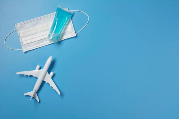 Ein Spielzeugflugzeug mit medizinischer Maske zum Schutz von Viren und Staub. Reise- und Schutzkonzept. – Foto