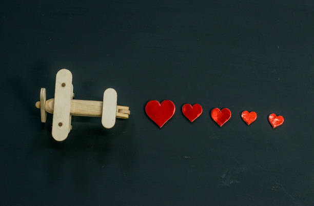 Toy airplane with trail of hearts on black background A small wooden airplane toy is flying from one side to the other. A trail of red hearts is behind the plane. long distance relationship stock pictures, royalty-free photos & images