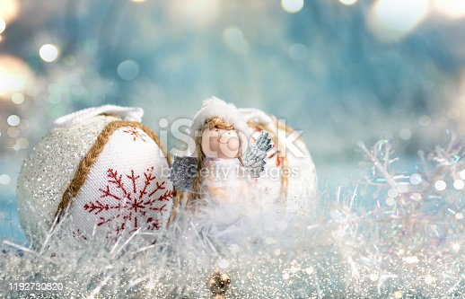 Toy Angel and festive Christmas decorative ball with abstract background