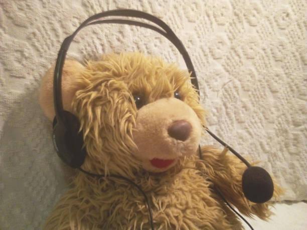 a toy bear cub responds by a headset - headphones and a microphone - call center стоковые фото и изображения