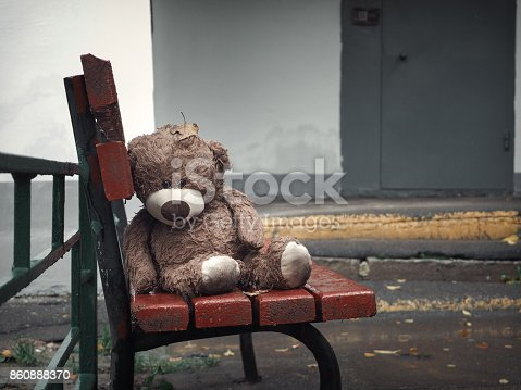 istock A toy bear is sad and wet on the bench at the entrance to the house 860888370