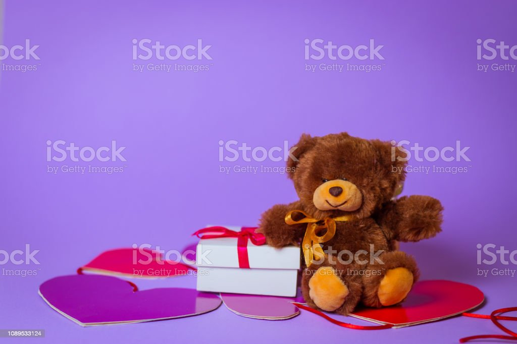 Toy Bear sits on paper hearts near a white gift box with a Red Ribbon...