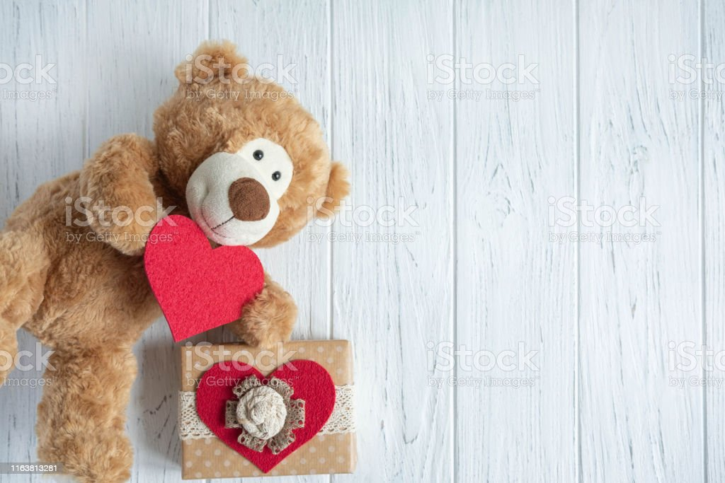Toy bear with a heart and boxes with gifts on a light wooden...