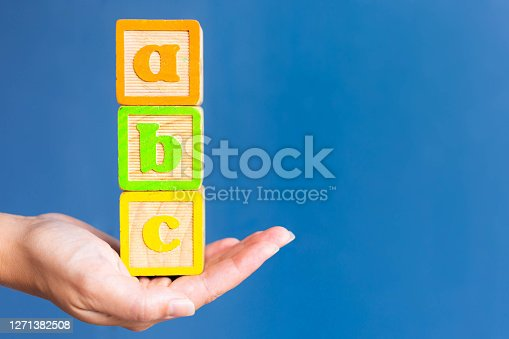 A hand holding abc toy blocks in front of a blue background with copy space.
