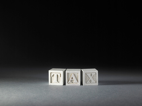 toy blocks with single word tax on black background