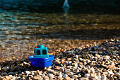 Small blue color focused toy boat on pebble beach.