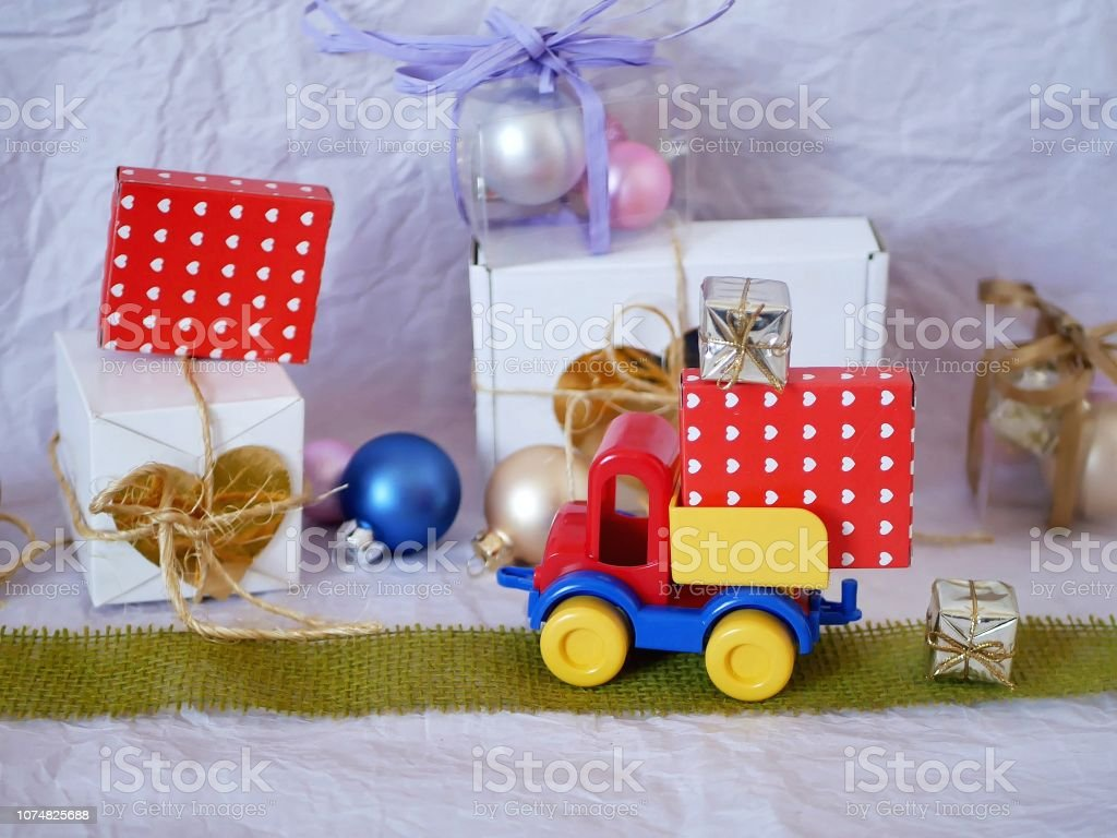 Toy bright car, boxes with gifts, Christmas decorations, New Year\'s...