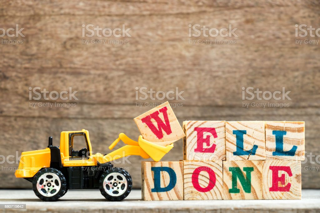 Toy bulldozer hold letter block w to complete word well done on wood background stock photo
