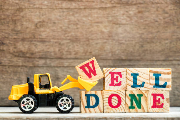 toy bulldozer hold letter block w to complete word well done on wood background - well done stock photos and pictures