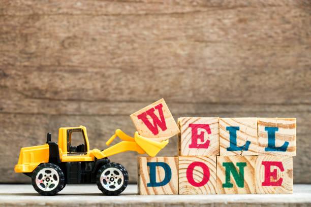 excavadora de juguete mantenga carta bloque w para completar palabra bien hecho sobre fondo de madera - agradecimiento fotografías e imágenes de stock