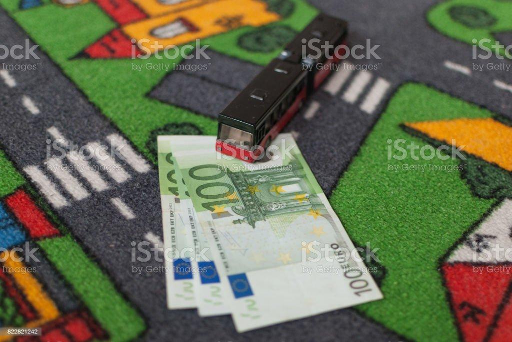 Toy bus parked on three 100 euro bills stock photo