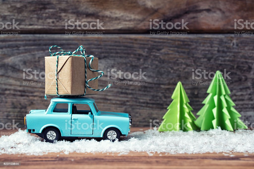 Toy car carrying Christmas gift with snow, paper fir trees stock photo
