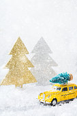 istock Toy car carrying christmas tree in a snow forest 1284204005