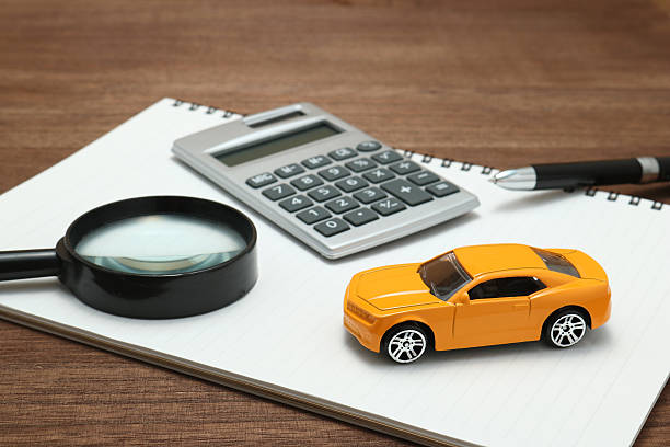 toy car, magnifying glass, calculator, pen and notebook. - sale lenses stock photos and pictures