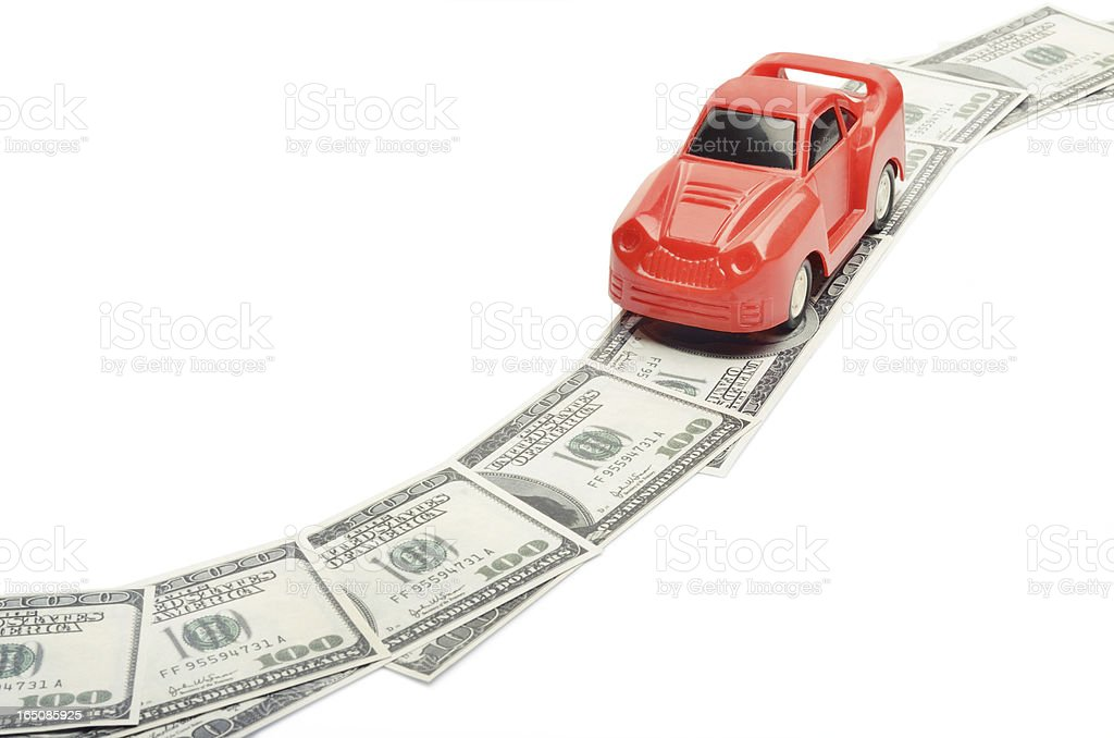 Toy car moving on a US paper currency road royalty-free stock photo