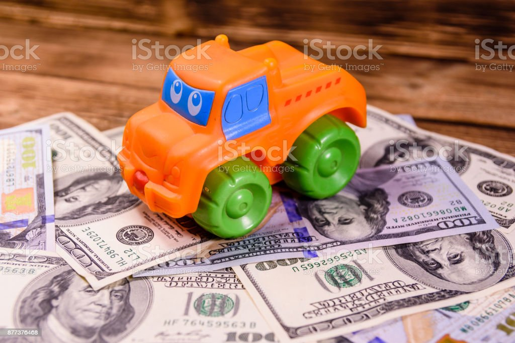 Toy car on a one hundred dollar bills stock photo