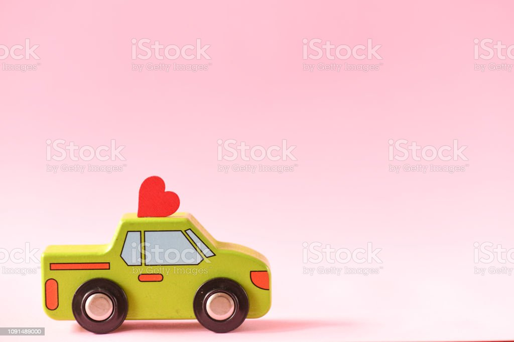 A toy car with a heart on the roof. February 14 a day of lovers. Valentine's background. stock photo