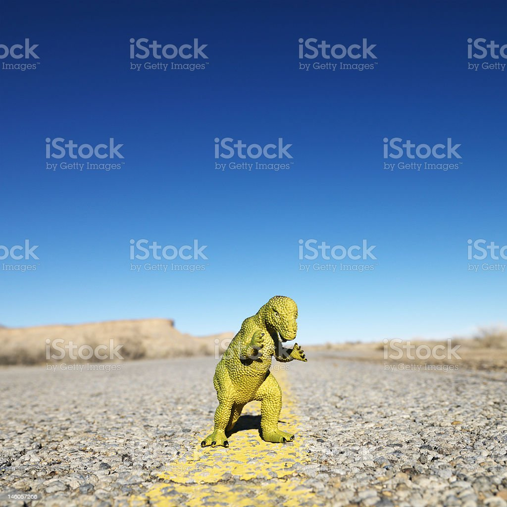 Toy dinosaur in road. stock photo