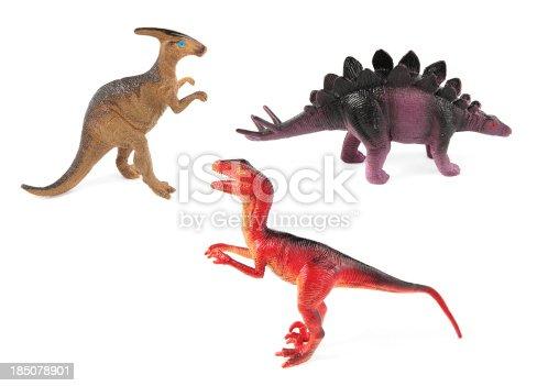 Three plastic toy dinosaurs on white