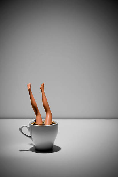 Toy doll in cup of coffee stock photo