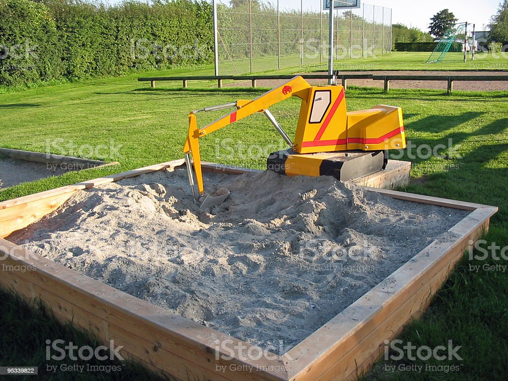 Toy excavator in a playground stock photo
