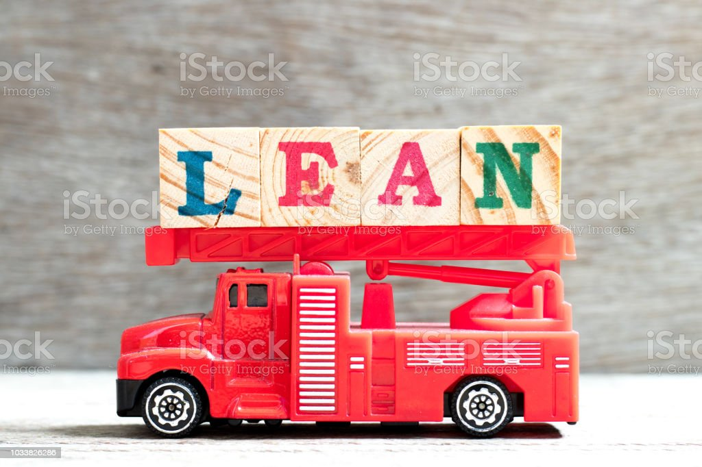 Toy fire ladder truck hold letter block in word lean on wood background stock photo